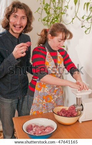 The man and the woman on kitchen prepare a mincemeat. - stock photo
