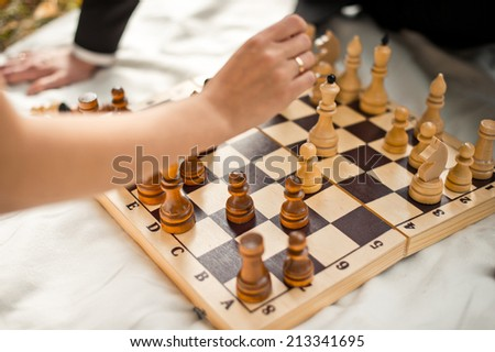 The man and the woman play chess outdoors. - stock photo