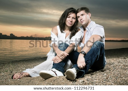 The man and the woman sit having embraced on a beach