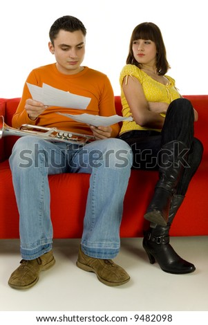 The man and the woman sitting on red couch. Man showing the woman sheet music. She looks insulted. White background.