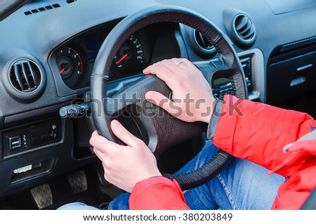The man at a car wheel. Hands of the man lie on a wheel. The man presses a signal on a wheel to the car. Management of transport. - stock photo