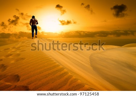 The man be ready to drop with weariness in desert. Sunset gold desert.