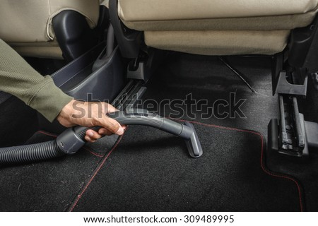 the man cleaning his car with vacuum cleaner - stock photo