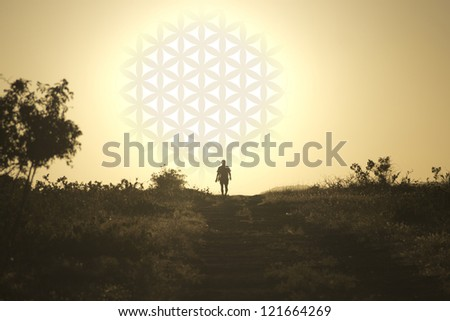 The man comes from the setting sun in the form of flower of life - stock photo