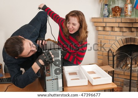 The man connects the new computer, and the woman helps. - stock photo