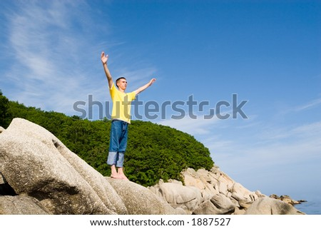The man costs(stands) on rocks having stretched hands. - stock photo