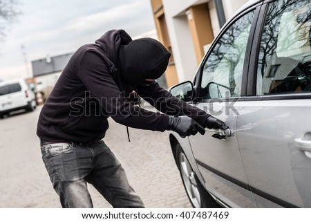 The man dressed in black with a balaclava on his head trying to break into the car. He uses a screwdriver. Car thief, car theft concept