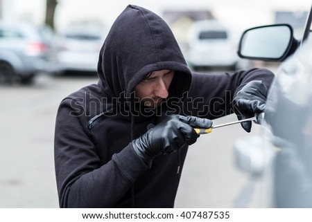The man dressed in black with a hood on his head trying to break into the car.  Car thief, car theft concept