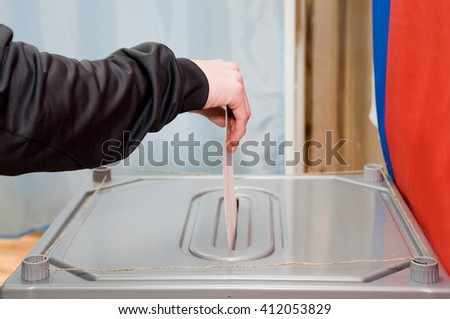 The man drops his ballot in the ballot box. Elections - stock photo
