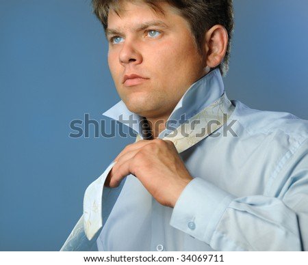 The man fastening necktie - stock photo