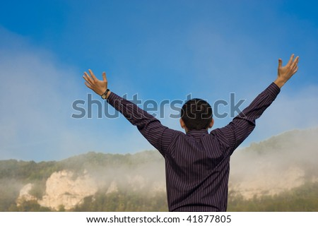 The man feels freedom. Over blue sky and mountains - stock photo