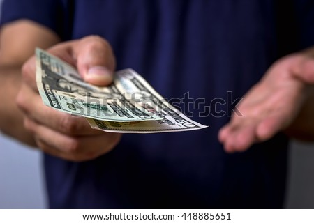 The man gives money. Hand holding out cash. - stock photo