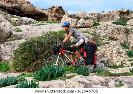 The man goes on a sandy beach on a mountain bike with a big backpack. Cyprus - stock photo