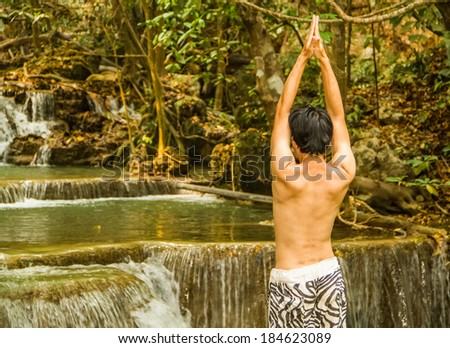 The man having yoga session at waterfall.