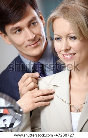 The man helps to try on to the woman of a necklace - stock photo