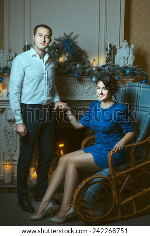 The man holding the hand of a woman who is sitting in a chair near the fireplace, in terms of burning candles. - stock photo