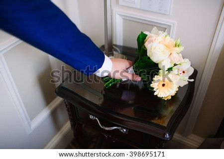 The man holds out his hand for the bouquet. The groom picks up the bouquet - stock photo