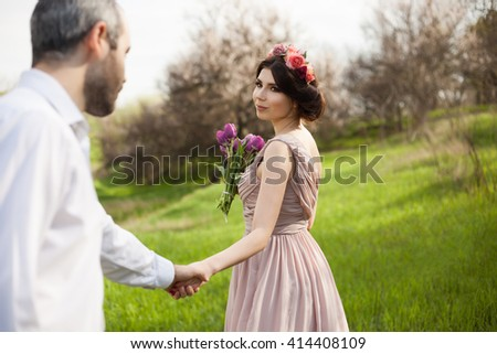 The man holds the hand of his young smiling bride. Gorgeous wedding couple portrait. Real feelings and real emotions. Beautiful young smiling brunette with wedding make up and floral crown in her hair - stock photo