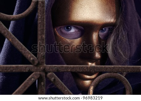 The man  in a gold mask behind a rusty fence - stock photo