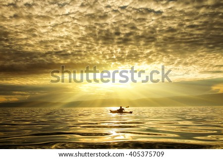 The man in a kayak on a sunset. Lake Baikal. - stock photo