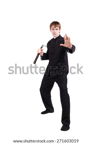The man in a kimono practicing kung fu. Master holding nunchuck. Fighter isolated on white background. Concept of healthy life and martial arts. - stock photo