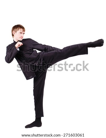 The man in a kimono practicing kung fu. Master rack side kick. Fighter isolated on white background. Concept of healthy life and martial arts. - stock photo