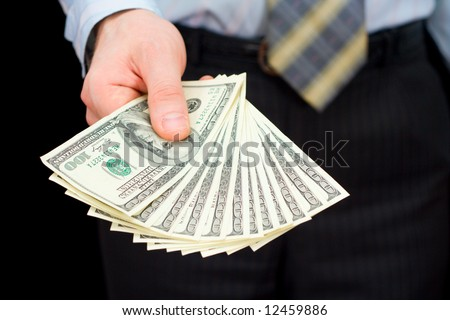 The man in a suit, offering a pack of dollars - stock photo