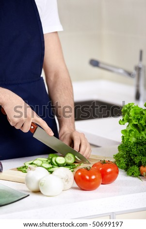 The man in an apron cuts cucumbers close up - stock photo