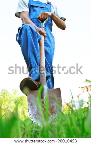 The man in dark blue overalls digs a shovel a ground - stock photo