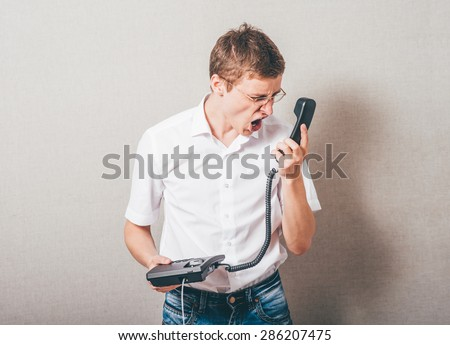 The man in glasses shouts into the phone wired telephone. On a gray background. - stock photo