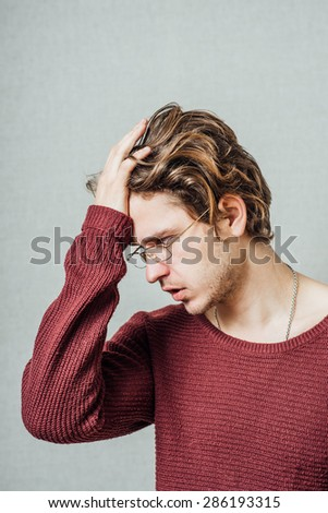 The man in glasses upset sad, hand on his head, his head lowered. On a gray background. - stock photo