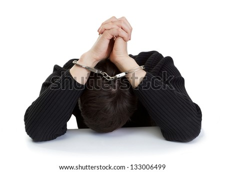 The man in handcuffs closes hands the head. - stock photo