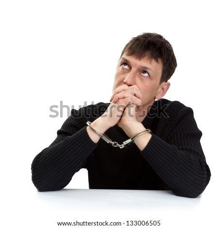 The man in handcuffs thoughtfully looks up. - stock photo