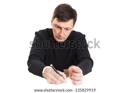 The man in handcuffs writes something a ball pen. - stock photo