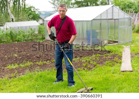 The man in overalls and protective glasses mowing grass