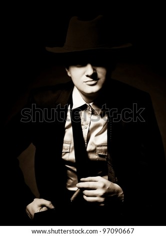 The man in style Chicago gangster with cigar on dark background - stock photo