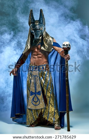 The man in the image of the ancient Egyptian Pharaoh  with a  mask of  Anubis on his face on blue background - stock photo