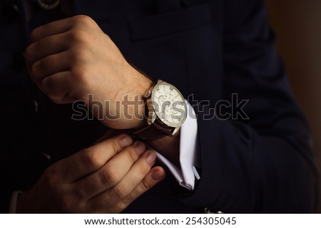 The man in the white shirt in the window wears watches. - stock photo