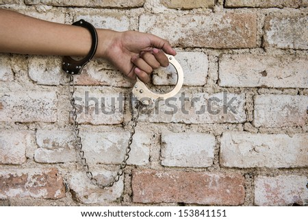 The man is arrested in jail with handcuffs - stock photo