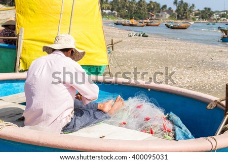 The man is mending nets fishing on the local a basket boat at Fishing village, a famous tourist destination in Mui Ne, Vietnam. - stock photo