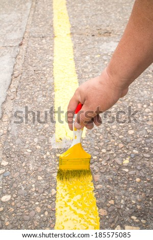 The man is painting the the yellow line on the concrete for car  - stock photo