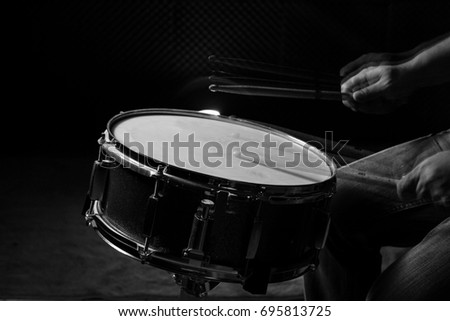 The man is playing snare drum in low light background, black and white.