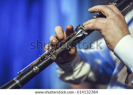 The man is playing the clarinet. Musician of middle age, European appearance. Hands close-up.