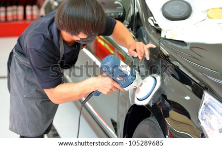 The man is polishing the black car with polish machine. - stock photo