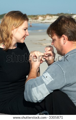 The man is proposing marriage to his girlfriend on the beach. She said Yes and he is putting a gold ring on her finger. The most romantic scene under the blue skies. - stock photo