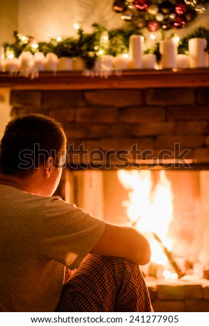 The man is sitting near the fireplace