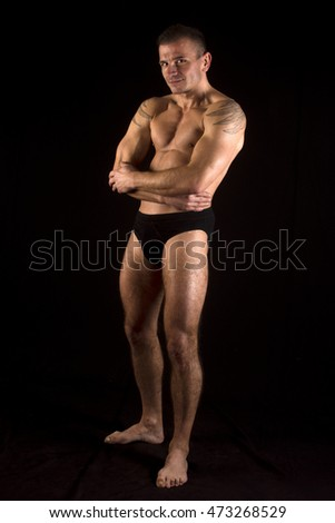 The man is standing in underwear on black background.