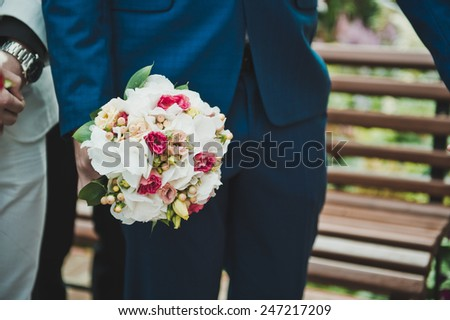 The man keeps a bouquet in a suit. - stock photo