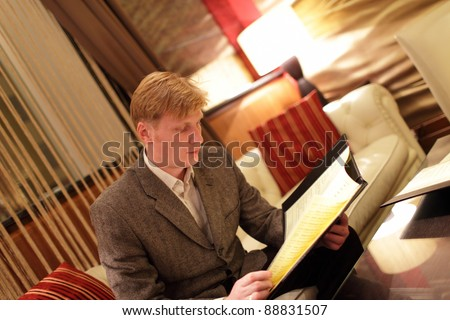 The man looking at a menu in hotel restaurant - stock photo