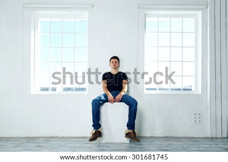 The man next to the window. One man sits with his back to the window. Fashionable male model. The empty space of the room around a man. Against the background of windows and light blue walls. - stock photo
